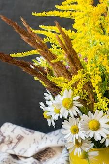 暗い背景上の花瓶に秋の花束