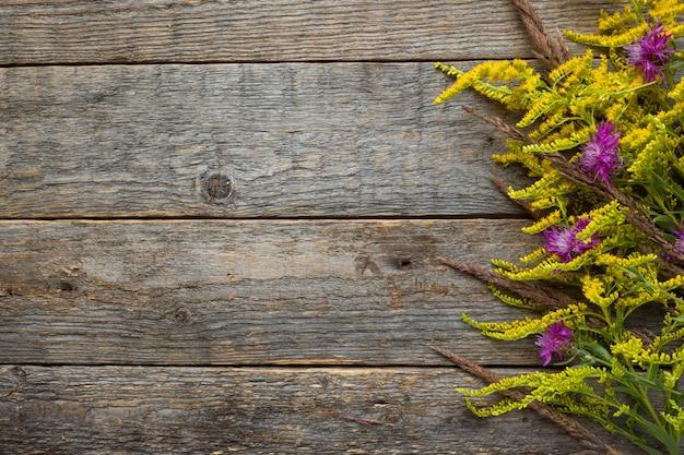 素朴な木製の背景に秋の花。コピースペース