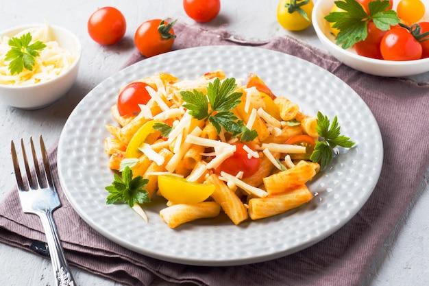 マカロニ、トマトソースのパスタ、木製テーブルの上の皿にチーズ