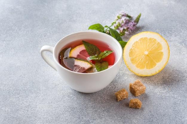 Чашка чая, мяты и лимона на сером столе с копией пространства