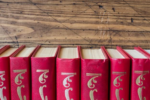 木製のテーブルの上のハードカバーの本のスタック。テキストのコピースペース