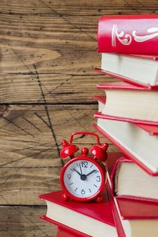 ハードカバーの本と木製のテーブルの上の目覚まし時計のスタック。テキストのコピースペース