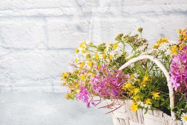 Букет красивых полевых цветов в корзине на серой поверхности с копией пространства.