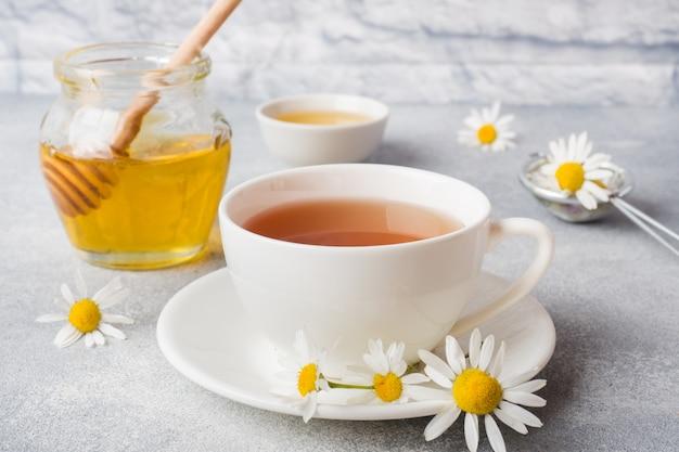 灰色のテーブルにカモミールの花とハーブティーのカップ。コピースペース