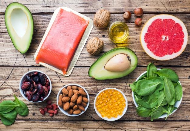 コンセプト健康食品抗酸化製品:魚とアボカド、ナッツと魚油、木製の背景にグレープフルーツ。