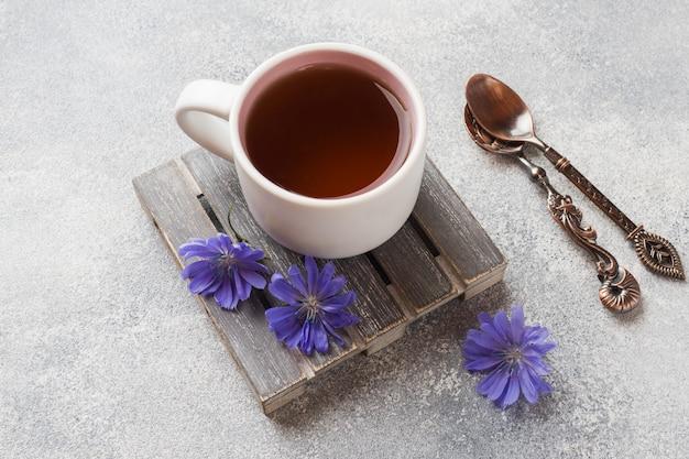 チコリの飲み物と灰色のテーブルの上の青いチコリの花のカップ