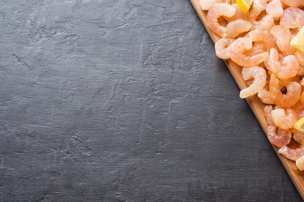 木の板にレモンとスパイスのエビ