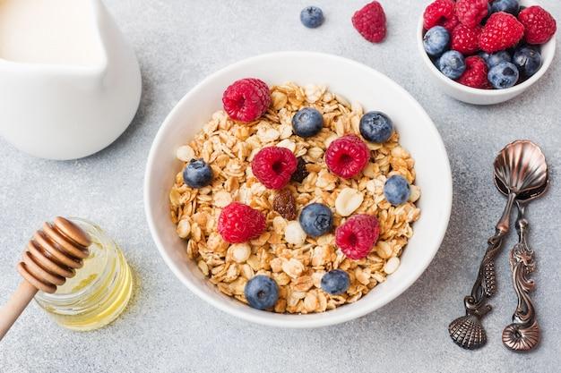 健康的な朝食。新鮮なグラノーラ、ミューズリー、ヨーグルト、灰色の背景上の果実。