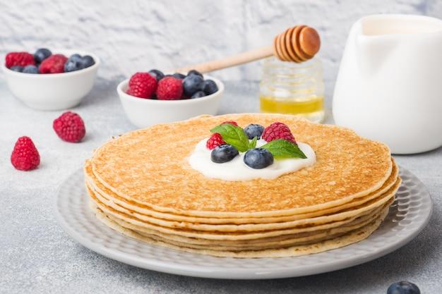 灰色のテーブルの上の果実とおいしい薄いパンケーキのプレート