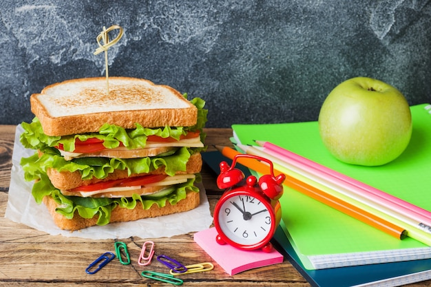サンドイッチ、新鮮なリンゴ、オレンジジュースと学校のヘルシーなランチ