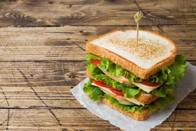 暗い木製のテーブルにおいしいと新鮮なサンドイッチ。