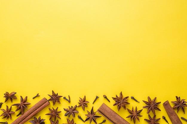 Композиция из звездчатого аниса, палочки корицы и гвоздики на желтом фоне