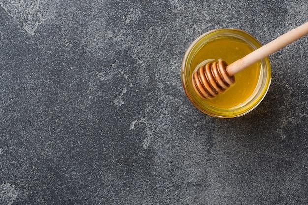 Жидкий мед и мед прилипают к серой поверхности.