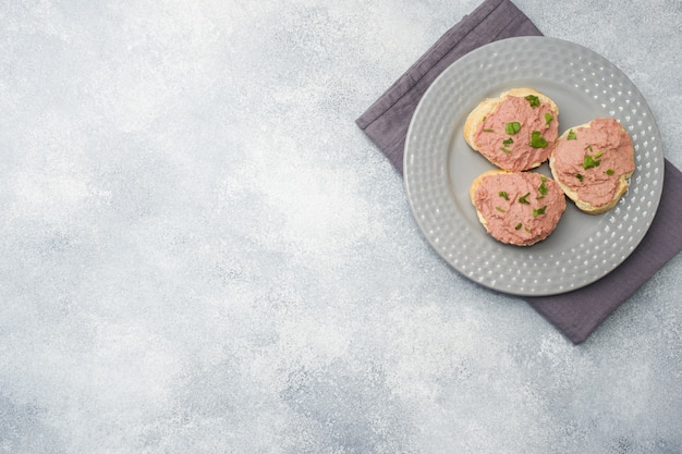 チキンパテとテーブルの上のバターのサンドイッチ。