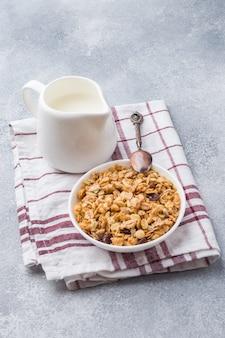 健康的な朝食は、ナプキンにミューズリーと牛乳を焼きました。