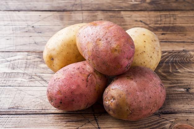 木製のテーブルに新鮮なジャガイモ。