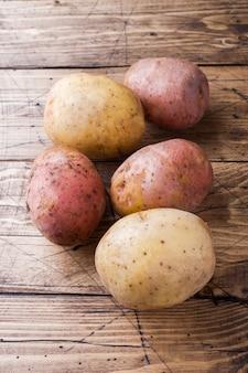 生のジャガイモの赤と黄色の食べ物。木製のテーブルに新鮮なジャガイモ。