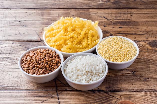 ひき割り穀物の食料品。木製のテーブルに米パスタそばとキビ。