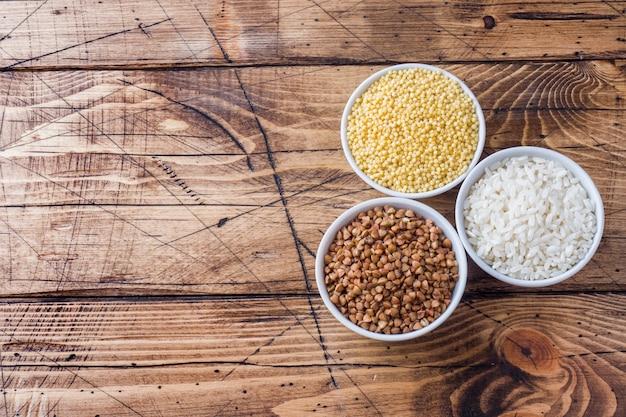 ひき割り穀物の食料品。木製のテーブルに米、そば、キビ。
