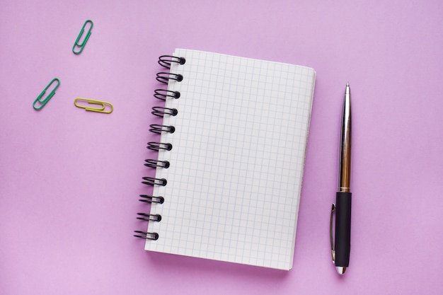 コピースペースを持つピンクのテーブル上のテキストのメモ帳。