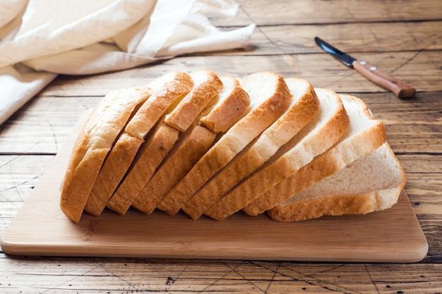 木製テーブルの上のトーストの白パンの部分。