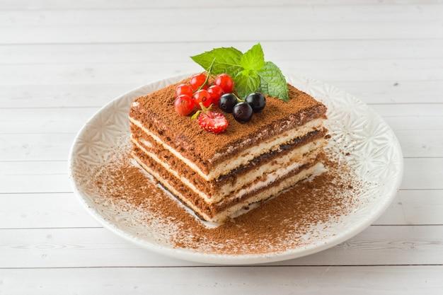 新鮮な果実と皿の上のミントのおいしいティラミスケーキ