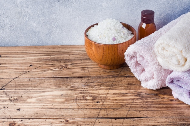 Махровое полотенце и косметическое масло для массажа.