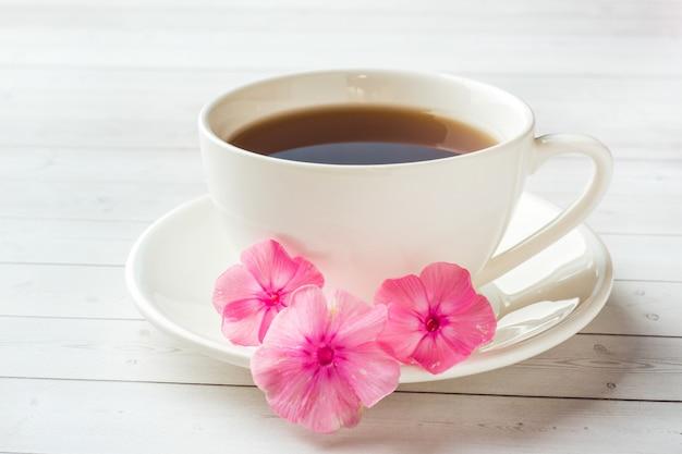 白いテーブルとピンクのフロックスの花のコーヒーカップ。