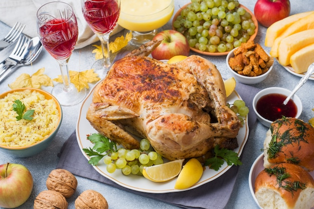 お祝いテーブルでのディナーには、焼きチキン、マッシュポテト、ワイングラスをお楽しみください。