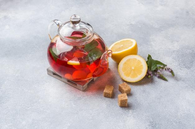 Стеклянный чайник с чаем, мятой и лимоном на сером столе с копией пространства.