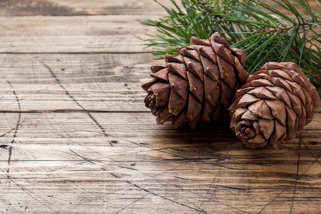 松ぼっくりと木製のテーブルに小ぎれいなな枝。