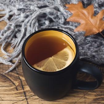 木製のテーブルにお茶、暖かい毛布、黄色の葉。