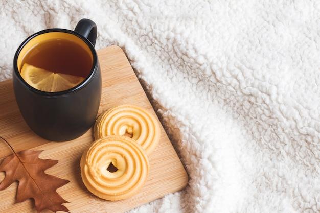 お茶、クッキー、セーター、暖かい柔らかい毛布の上の葉のある秋の静物。
