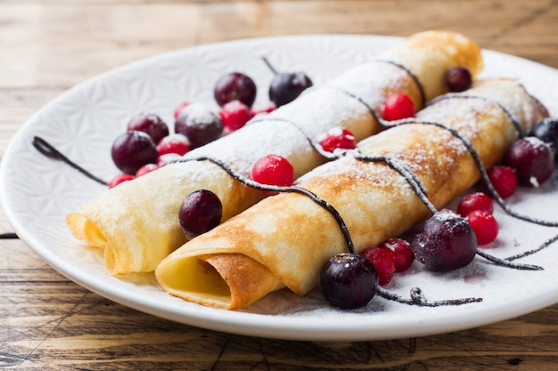 チョコレートと皿の上の果実のパンケーキチューブ。木製の背景