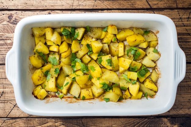 ジャガイモはスパイスとハーブを使ったセラミックのベーキングトレイで焼いたベジタリアン料理