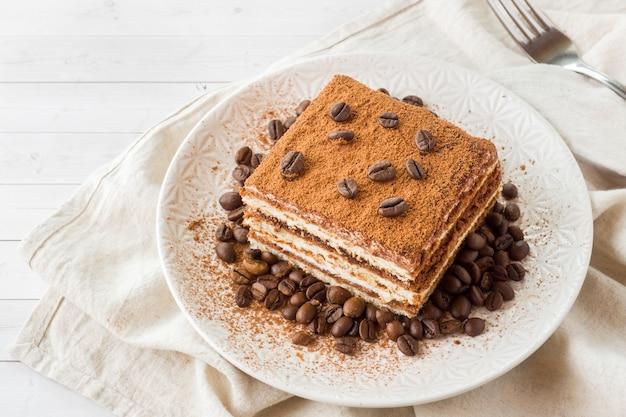 皿の上のコーヒー豆とおいしいティラミスケーキ