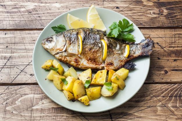 レモングリーンと皿の上のジャガイモと焼き魚の鯉。木製の背景