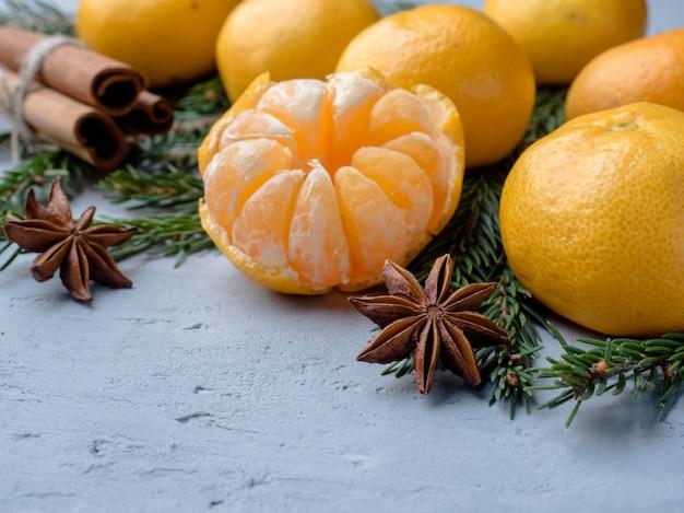 Свежие мандарины с ветвями елки, анисом и корицей на сером бетоне