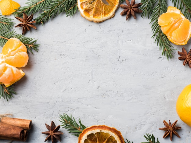 クリスマスツリーの枝と新鮮なみかん、灰色のコンクリートにスターアニスシナモン、コピースペース