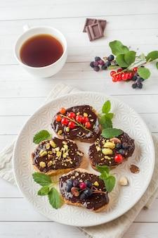 プレート上のチョコレートペースト、ピスタチオナッツ、新鮮なベリーのサンドイッチ。
