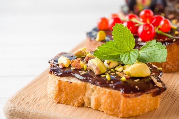 木製のサービングボードにチョコレートペースト、ピスタチオナッツ、新鮮なベリーのサンドイッチ。