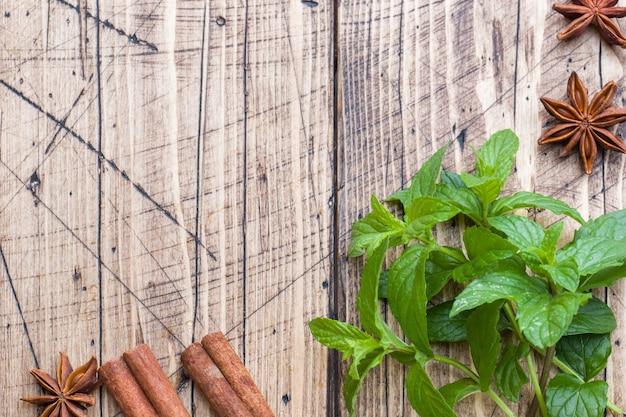 緑の新鮮なミント、スパイスシナモン、アニスの木製テーブル