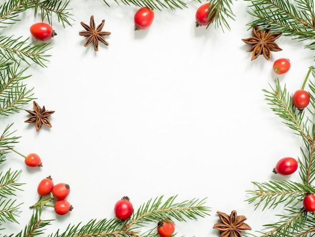白のクリスマスデコレーション、ベリーローズヒップ、星、モミの枝。