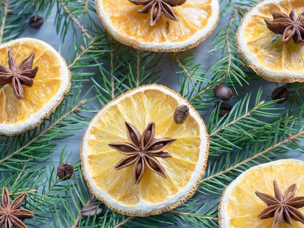 オレンジスライスの柑橘系の果物とスプルースの枝にスターアニスのクリスマス背景。