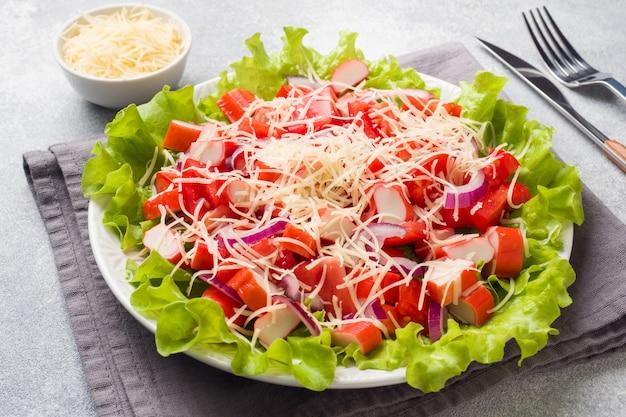 Вкусный салат из крабовых палочек с помидорами черри и тертым сыром с луком в блюдо.