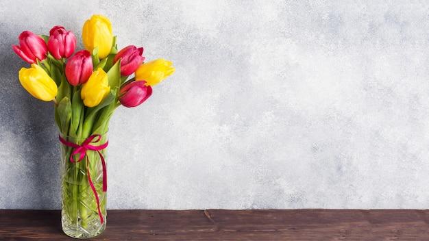 灰色の花瓶に黄色とピンクのチューリップの花束。製品とテキストのコピースペース。