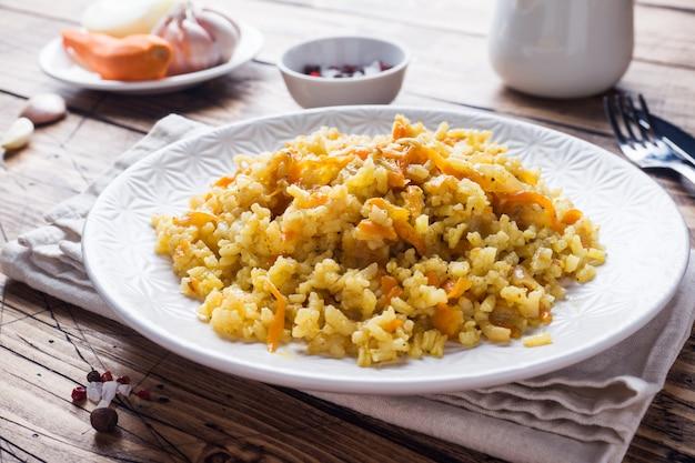 Вегетарианский восточный плов с рисом и овощами на деревянном столе.