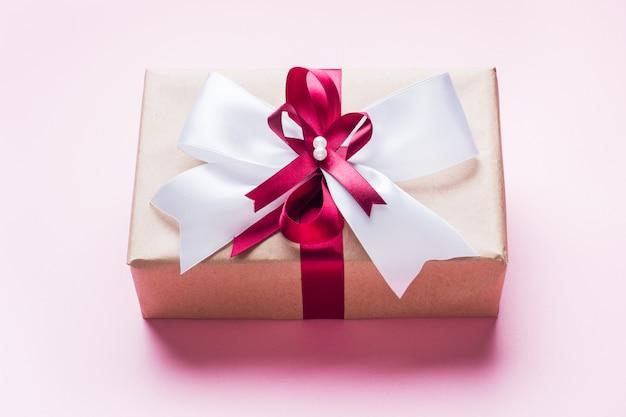 ピンクのテーブルトップビューに大きな弓のギフトボックスまたはプレゼントボックス。クリスマス、誕生日、母の日、結婚式のフラットレイアウト構成。
