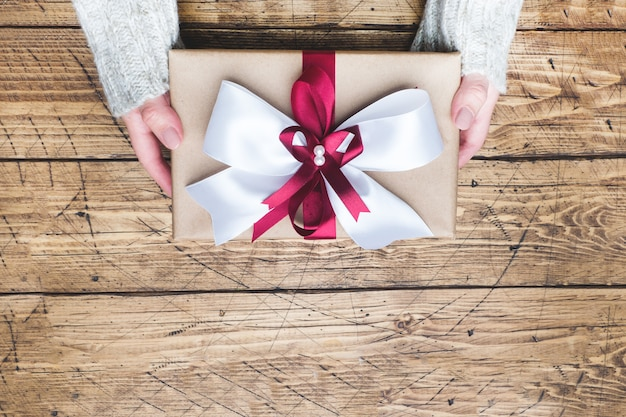 セーターを着た女性の手に大きな弓が付いたギフトまたはプレゼントボックス。クリスマス、誕生日、母の日、結婚式のフラットレイアウト構成。