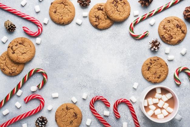 Шоколадное печенье, рождественская тростниковая карамель, чашка какао и зефирные шишки, украшения на сером. рамка